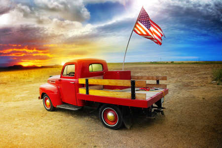 Red vintage pick up truck with American flag in wide open country side with dramatic sunset cloudscape  photo