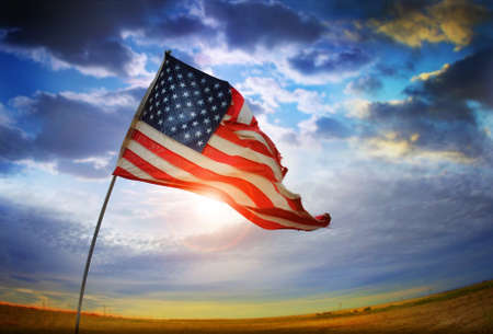 juli: Groothoek schot van een gescheurde Amerikaanse vlag waait in de wind tegen een mooie cloudscape