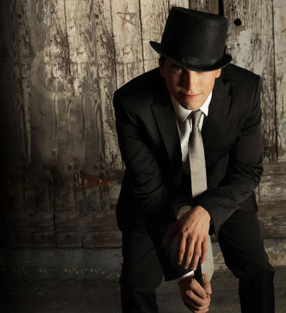 Fashion portrait of young male model in top hat and cane against grunge wall background