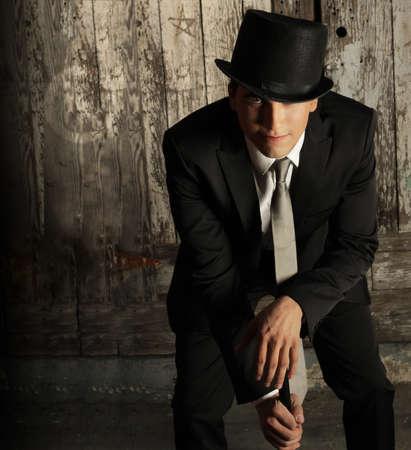 young male model: Retrato de moda de la joven modelo masculino en el sombrero y ca�a con antecedentes de pared grunge
