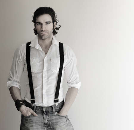neutral face: Portrait of an attractive relaxed male model in white shirt, suspenders, and jeans with his hands in pockets Stock Photo