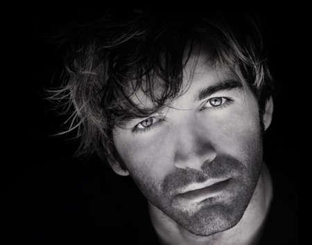 gezicht: Fine art close-up zwart en wit portret van mooie jonge man gezicht tegen zwarte achtergrond