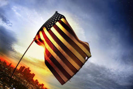 Wide angle photo of a tattered American flag blowing in the wind over a distant city lit by golden sunset light  Banco de Imagens