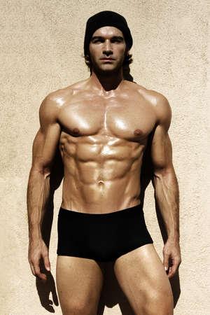 hombres musculosos: Sexy retrato de un modelo masculino sin camisa muy musculoso, mirando de lejos