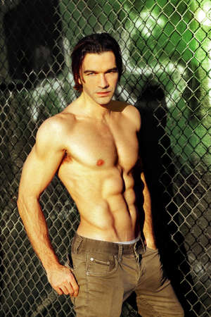 Sexy male fashion model shirtless against graffiti and fence Stock Photo - 9789942