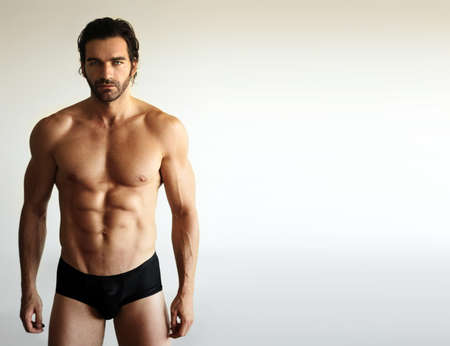 Portrait of a sexy male fitness model in underwear against neutral background with lots of copy space Stock Photo - 9789934