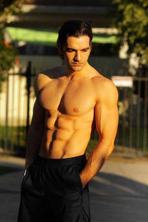 屋外のポートレートの黄金の夏の光の中で下へ見ている若い上半身裸の男性フィットネス モデル
