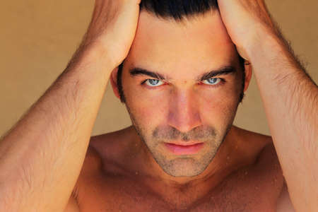 Closeup portrait of an attractive male model with hands on his head photo