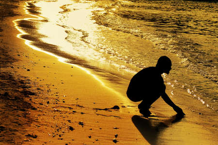 silhoutted: A silhoutted male figue bending down touching ocean water at coastline in golden sunset light