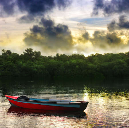 rowboat: A single red rowboat on a beautiful lake with dramatic sky and water reflections in morning light Stock Photo