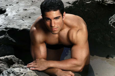builder: Attractive male muscular fitness model on the beach with rocks Stock Photo