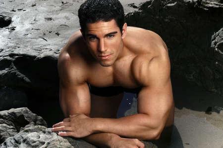 constructeur: Mod�le attrayant fitness musculaire m�les sur la plage avec les roches Banque d'images