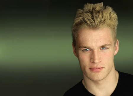 Portret van een jonge goed uitziende mannelijke model tegen de moderne donkere groene achtergrond