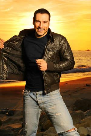 Full Body portret van mooie man in gouden licht draagt een leren jas tegen de prachtige zonsondergang