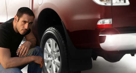 Portrait of a man kneeling down by large pickup truck photo