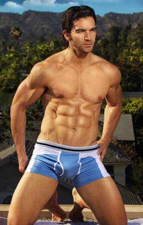 ropa interior: Retrato de verano al aire libre de un modelo masculino gorgeous en pantalones cortos azules Foto de archivo