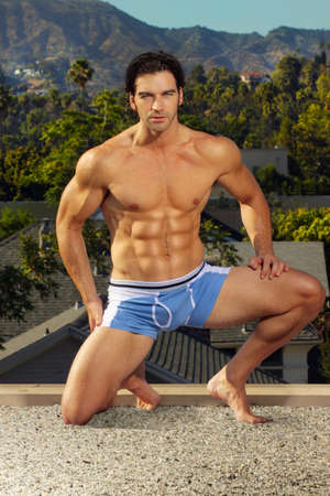Outdoors portrait of an incredibly fit suntanned male model in blue shorts photo