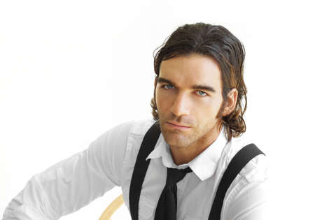 Portrait of a stylish young businessman in white shirt, black tie and suspenders against white background