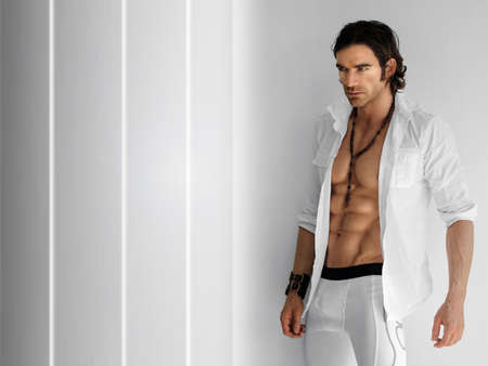 Portrait of a handsome fitness model wearing open crsip white shirt and white long boxer briefs against modern background