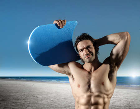 male surfer: Fun portrait of a young muscular male surfer on the beach with blue sky and ocean in background