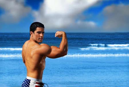 Young muscular sexy male body builder flexing his big bicep on the beach against a bright blue ocean and sky wearing USA flag swim trunks photo