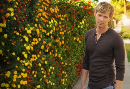 Portrait of a young man outdoors with beautiful flowers in background photo