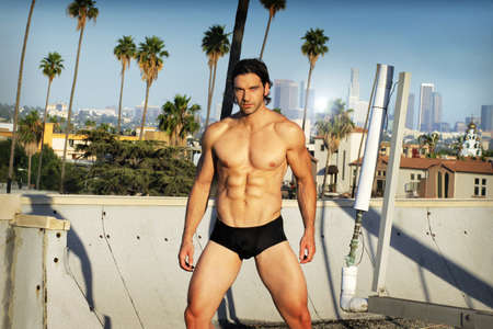 Body portrait in natural light of a young male fitness model in black briefs on Los Angeles rooftop photo