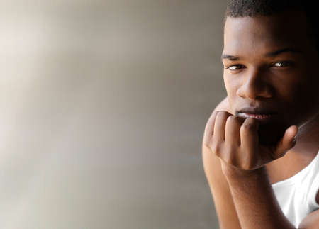 Portrait of a young black man thinking against neutral modern background with copy space
