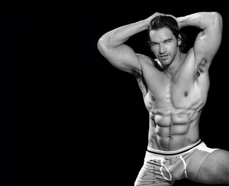 Black and white fine art  portrait of a sexy male fitness model posing and flexing with lots of copy space photo