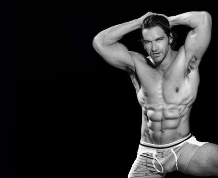 fine art portrait: In bianco e nero Arte del ritratto di un modello maschile in posa sexy fitness e la flessione con un sacco di spazio copia