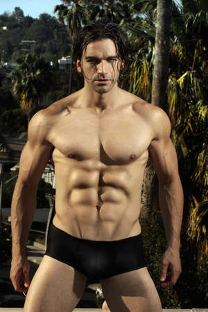 Body portrait of a sexy male fitness model in black briefs with muscular chest and six pack abs against lush outdoor background photo