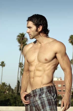 Body portrait in natural light of a good looking casual shirtless male model looking off