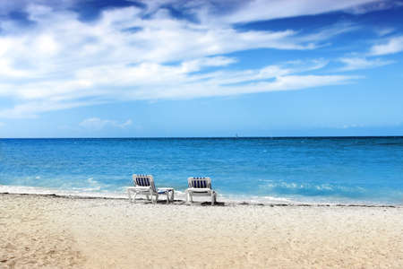 Two blue and white beach chairs on tropical white sand beach with bright blue sky photo
