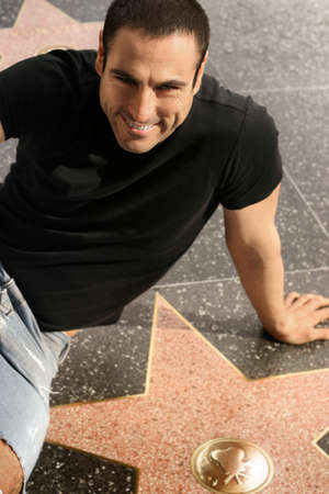 walk of fame: Man smiling posing with a star on Hollywood walk of fame Stock Photo