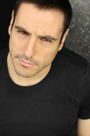 Closeup portrait of a serious man making expression in black shirt photo