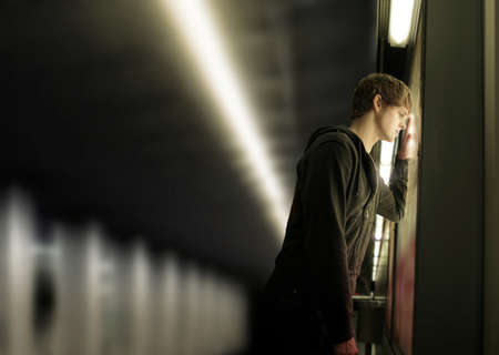 mood: Portrait of a young depressed man in subway station
