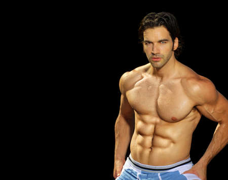 Sexy male fitness model on black background with lots of copy space Stock Photo - 10000676