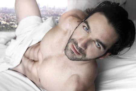 hombre desnudo: Hombre sexy desnuda en la cama cubierta con sábanas blancas y una ventana con vista a la ciudad en el fondo Foto de archivo