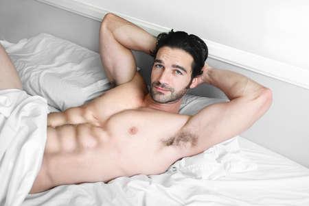 musculoso: Joven modelo muscular tumbado en la cama con sonrisa sexy Foto de archivo