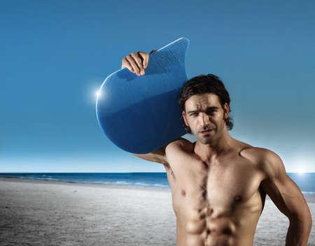 hombres sin camisa: retrato de un hombre musculoso joven en la playa con el cielo azul y el océano en el fondo Foto de archivo