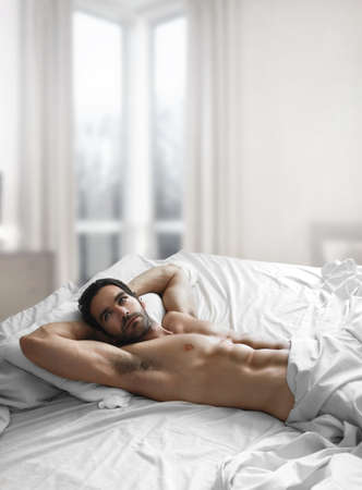 hombre desnudo: Retrato de un hombre desnudo sexy en dormitorio Foto de archivo