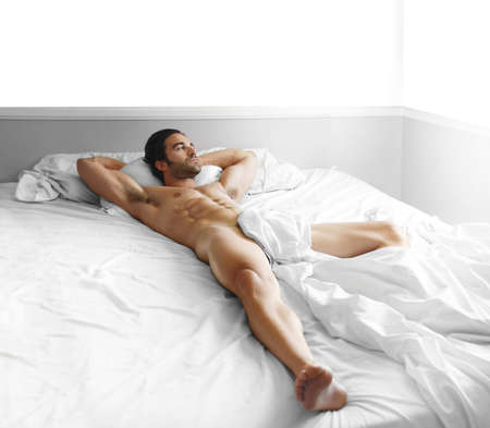 Full length portrait of a gorgeous sexy nude male model laying in bed Stock Photo - 10000726