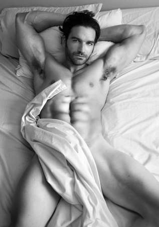 nude man: Fine art black and white body portrait of a nude male model in bed