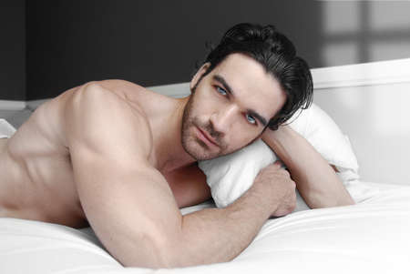 lying on the stomach: Sexy male model alone in bed