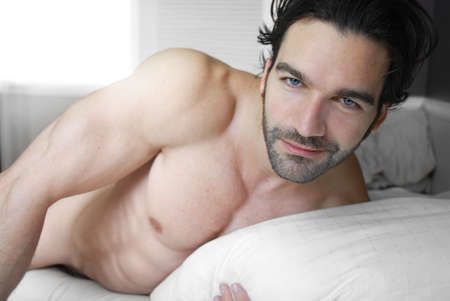 Happy playful young man shirtless in bed
