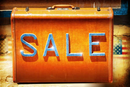Vintage leather suitcase with the word sale in metal on it photo