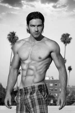Black and white photo of a classically handsome shirtless male model outdoors photo