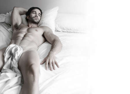 Beautiful young nude muscular male model alone in bed with lots of white copy space Stock Photo
