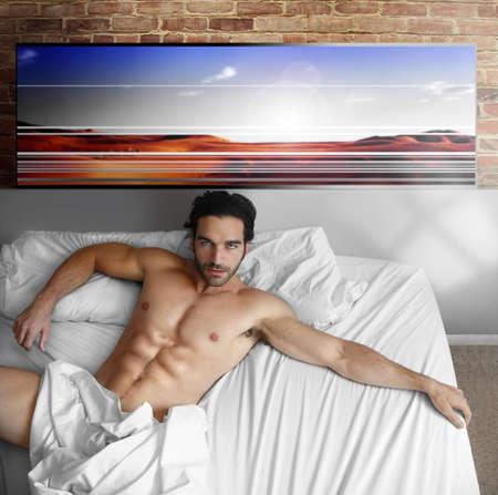 desnudo masculino: Sexy modelo masculino desnudo tendido en cama grande en casa en interior loft cool Foto de archivo