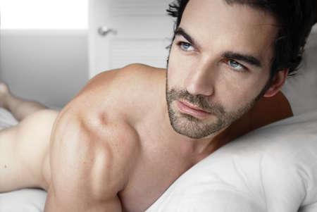 desnudo masculino: Sexy modelo masculino desnudo en la cama solo Foto de archivo